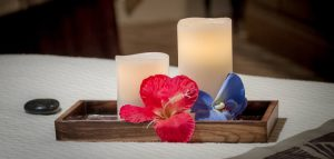 White candles with pink and blue flowers in wooden box
